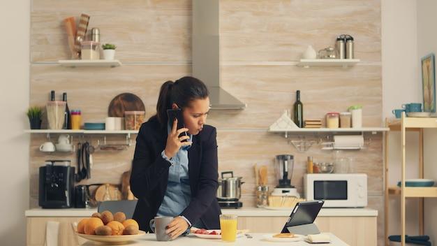 Freelancer spóźnia się do pracy, jedząc w pośpiechu śniadanie. skoncentrowana kobieta biznesu rano wielozadaniowość w kuchni przed wyjściem do biura, stresujący tryb życia, kariera i cele do