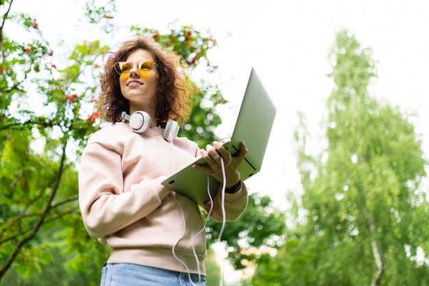 Freelancer stoi w parku z laptopem i słuchawkami w centrum parku wśród drzew