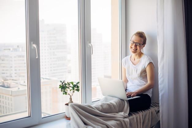 Freelancer szczęśliwy młody dorosły kobieta w okularach siedzi na tle okna. roześmiana blondynka pracuje na laptopie. miejsce pracy na parapecie. koncepcja biura domowego.