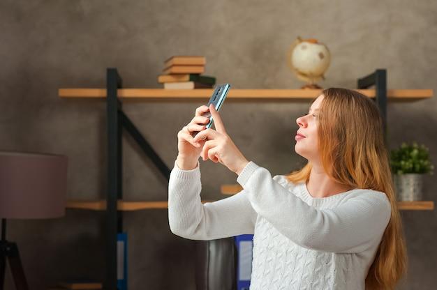 Freelancer w ciąży w biurze z telefonem.