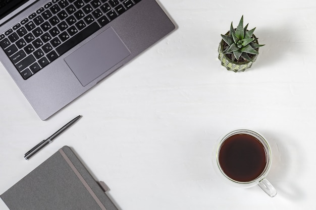 Freelancer w miejscu pracy. szary nowoczesny laptop z rosyjską klawiaturą, filiżanką kawy, metalicznym długopisem