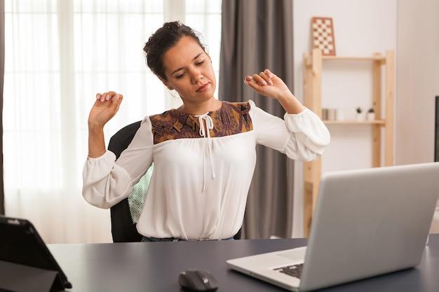 Freelancer z bólem pleców podczas pracy na laptopie z domowego biura.