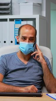 Freelancer z maską ochronną rozmawia przez telefon komórkowy z partnerami, siedząc na biurku w biurze podczas pandemii. freelancer pracujący w nowym, normalnym biurze, rozmawiający na czacie, mówiący na smartfonie