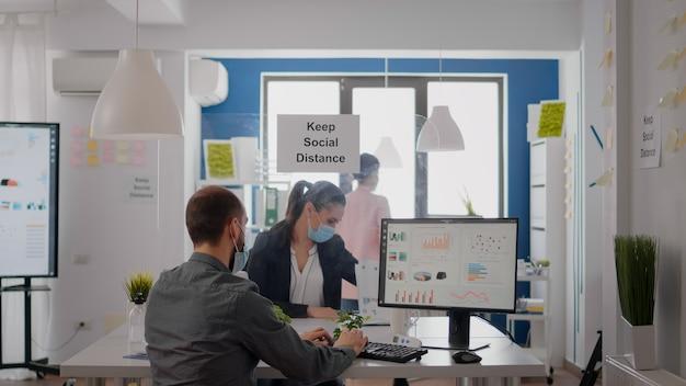 Freelancer z maską, pracujący w grafice finansowej na komputerze, siedzący w biurze firmy. współpracownicy rozmawiający w tle o marketingu utrzymują dystans społeczny, aby zapobiec zarażeniu covid19