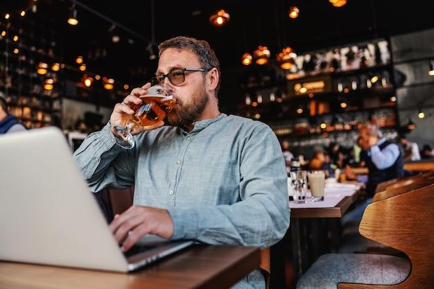 Freelancer z okularami siedzi w barze, pije świeże zimne piwo i pisze na laptopie.
