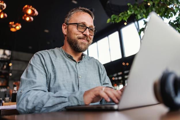Freelancer z okularami siedzi w restauracji i używa laptopa do pisania raportu