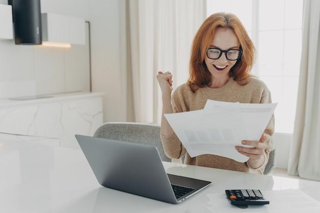 Freelancerka sprawdza obliczenia, zaciska pięści, radośnie patrzy na papierowe dokumenty