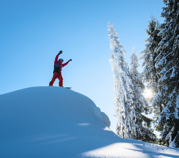 Freerider męski snowboarder stojący na szczycie stoku narciarskiego