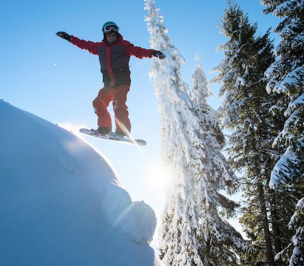 Freerider snowboarder skoki w powietrzu podczas jazdy na stoku w górach. błękitne niebo i słońce. koncepcja sezonu narciarskiego i sportów zimowych