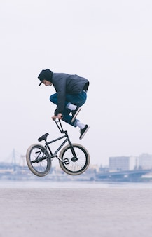 Freestyle bmx. młody człowiek wykonuje sztuczki powietrzne na rowerze bmx. w krajobrazie miejskim