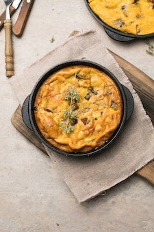 Frittata z grzybami na patelni na podłoże drewniane. fritata to włoskie danie śniadaniowe.