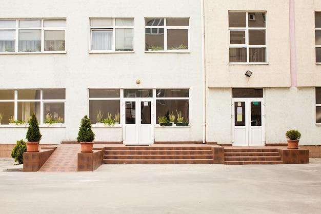 Frontowe wejście do budynku szkoły z ukraińską flagą obok drzwi