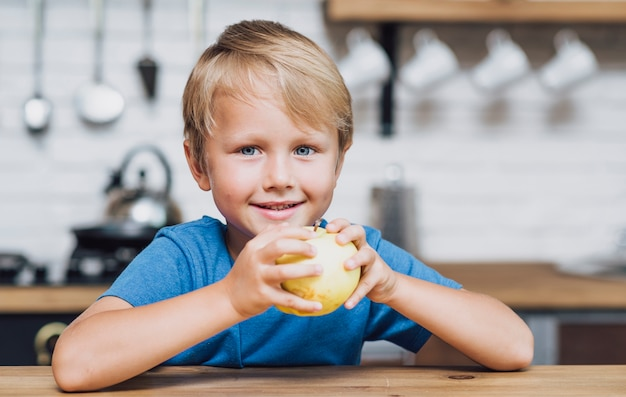 Frontowego widoku blondynki chłopiec je jabłka