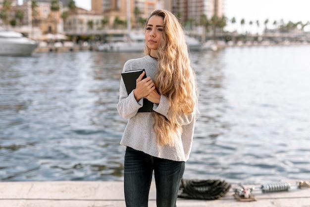 Frontowego widoku blondynki kobieta trzyma książkę