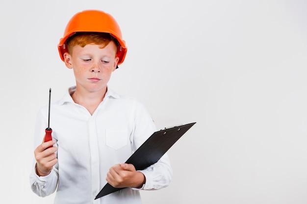 Frontowego widoku dziecko pozuje jako pracownik budowlany