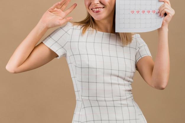 Frontowego widoku kobieta uśmiecha się miesiączka stół i trzyma