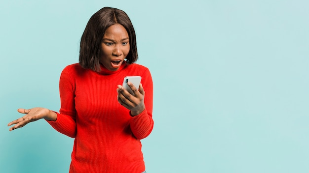 Frontowego widoku kobieta z smartphone w studiu