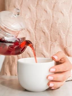 Frontowego widoku kobiety dolewania herbata w białej filiżance