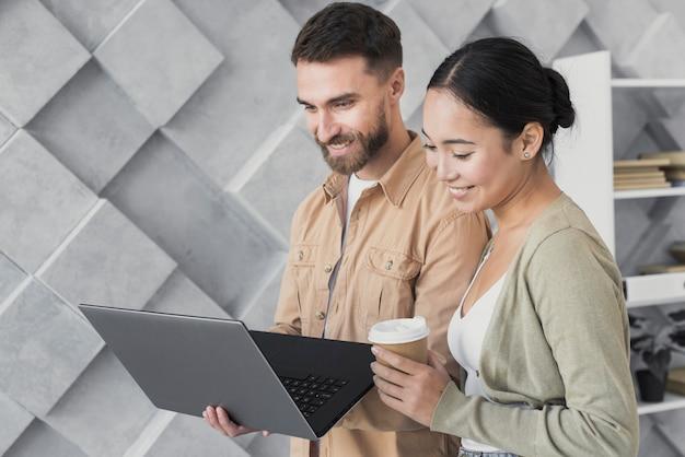 Frontowego widoku kolega patrzeje laptop przy pracą