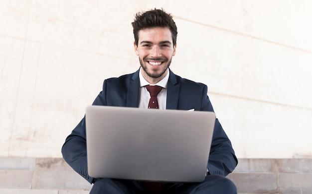 Frontowego widoku mężczyzna patrzeje kamerę z laptopem