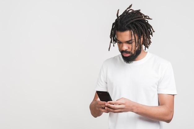Frontowego widoku mężczyzna patrzeje na jego smartphone
