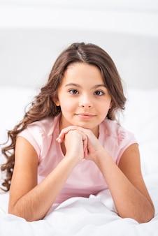 Frontowego widoku młoda dziewczyna zostaje w łóżku w domu