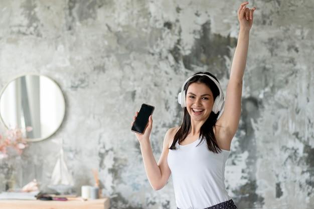 Frontowego widoku młoda kobieta cieszy się słuchać muzyka