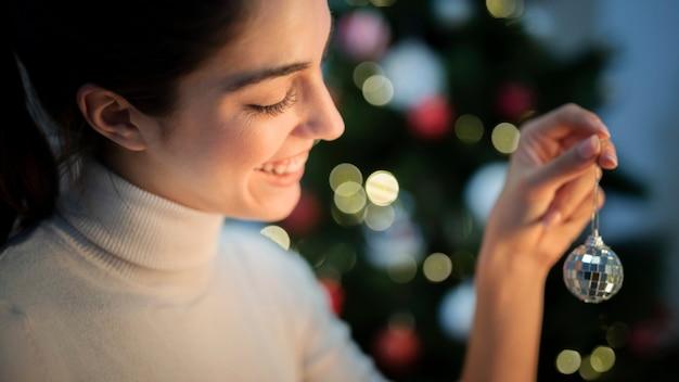 Frontowego widoku młoda kobieta dekoruje drzewa z kulą ziemską