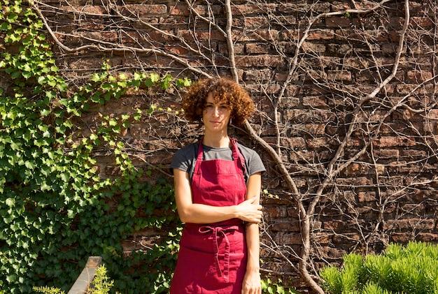 Frontowego widoku młoda kobieta pozuje obok rośliien