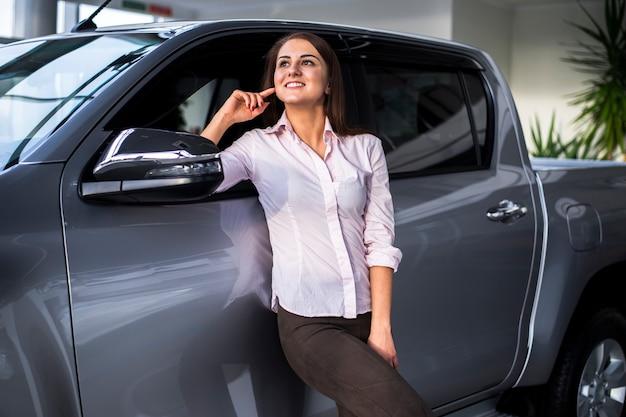 Frontowego widoku młoda kobieta pozuje obok samochodu