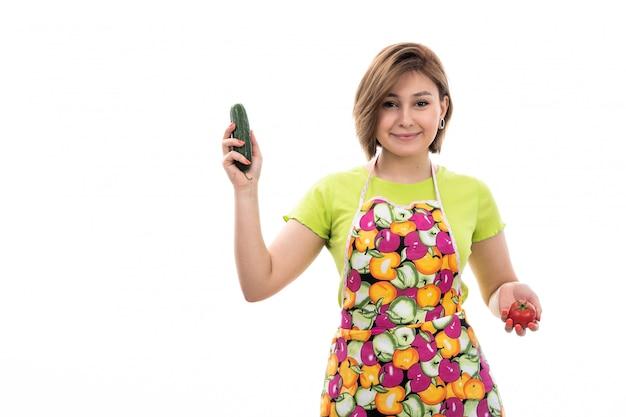 Frontowego widoku młoda piękna gospodyni domowa w zielonego koszulowego kolorowego przylądka mienia uśmiechniętych warzywach na białym tło domu czyści kuchnię
