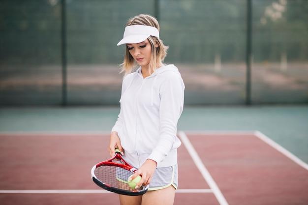 Frontowego widoku młody gracz w tenisa na polu