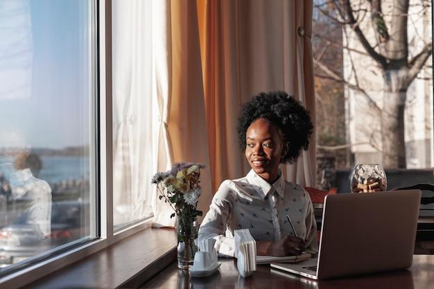 Frontowego widoku nowożytna kobieta przy biurkiem pracuje na jej laptopie