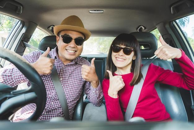 Frontowego widoku pary azjatykci szczęścia obsiadanie w samochodowego przedstawienia kciuku up.