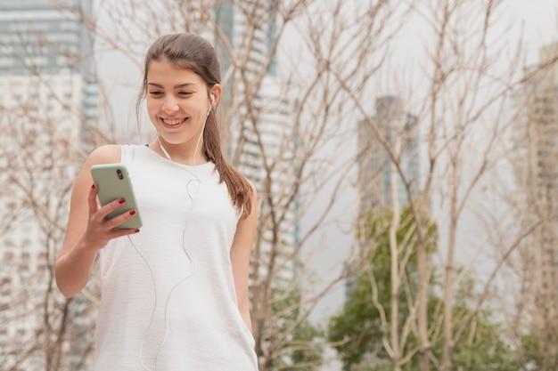 Frontowego widoku smiley kobieta trzyma jej telefon