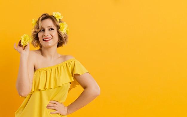 Frontowego widoku smiley kobieta z żółtymi kwiatami