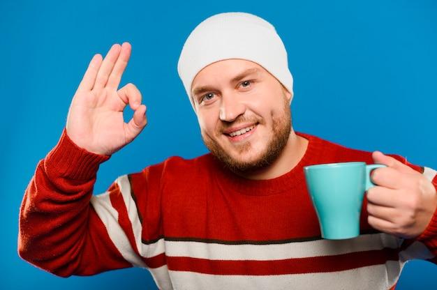 Frontowego widoku smiley mężczyzna trzyma filiżankę herbata