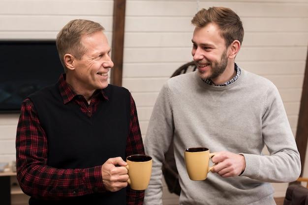 Frontowego widoku smiley ojciec i syn pozuje podczas gdy trzymający filiżanki