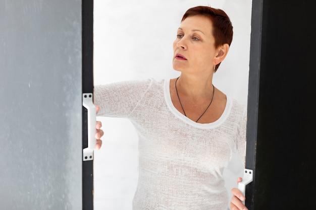 Frontowego widoku starsza kobieta patrzeje daleko od