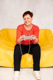 Frontowego widoku starsza kobieta patrzeje na telefonie i słuchającej muzyce