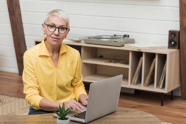 Frontowego widoku starsza kobieta patrzeje przez interneta na jej laptopie