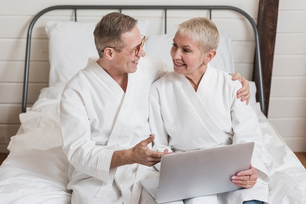 Frontowego widoku starsza para patrzeje na laptopie w łóżku wpólnie