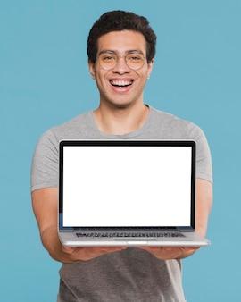 Frontowego widoku student uniwersytetu trzyma laptop
