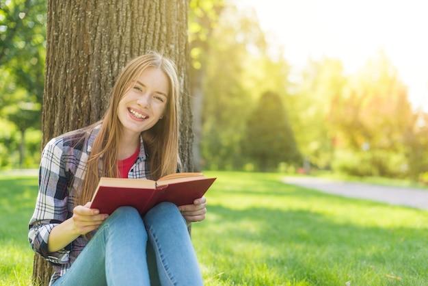 Frontowego widoku szczęśliwa dziewczyna czyta książkę podczas gdy siedzący na trawie