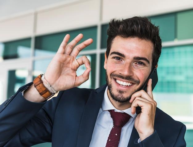 Frontowego widoku szczęśliwy mężczyzna pokazuje zatwierdzenie