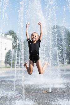 Frontowy widok bawić się przy fontanną dziewczyna