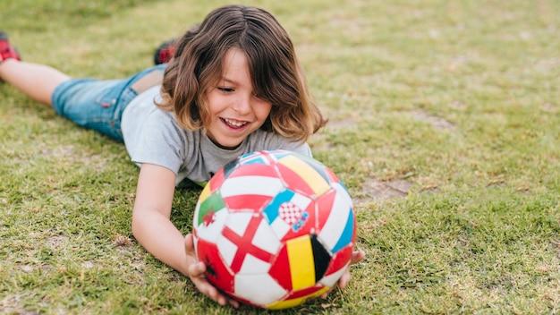 Frontowy widok bawić się w trawie chłopiec