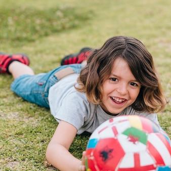 Frontowy widok bawić się w trawie dzieciak