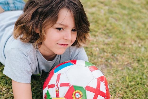 Frontowy widok bawić się w trawie dziecko
