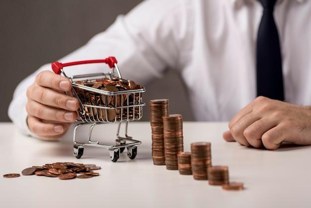Frontowy widok biznesmena mienia wózek na zakupy z monetami